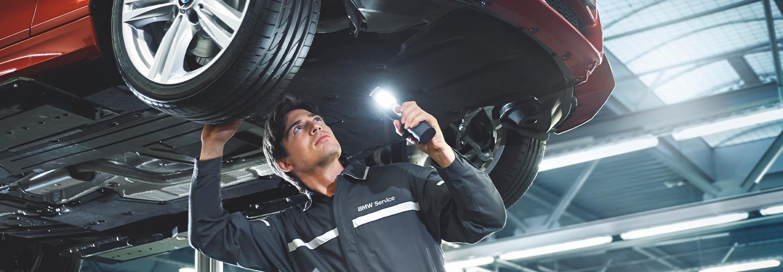 Service technician working under a BMW