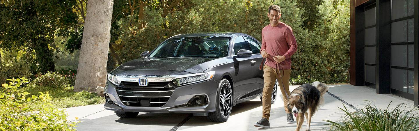 A man walking a dog next to the 2021 Accord