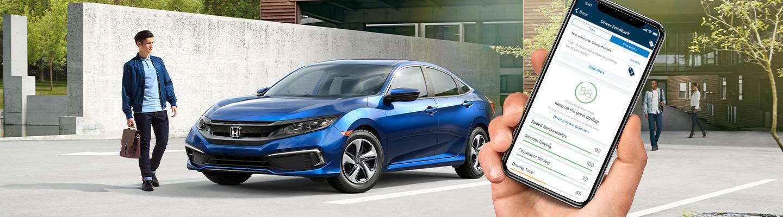Honda driver walking next to a new Honda from South Motors Honda using the Hondalink app.
