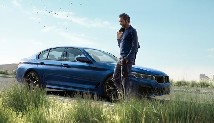A man standing next to a blue 2021 BMW 5 Series
