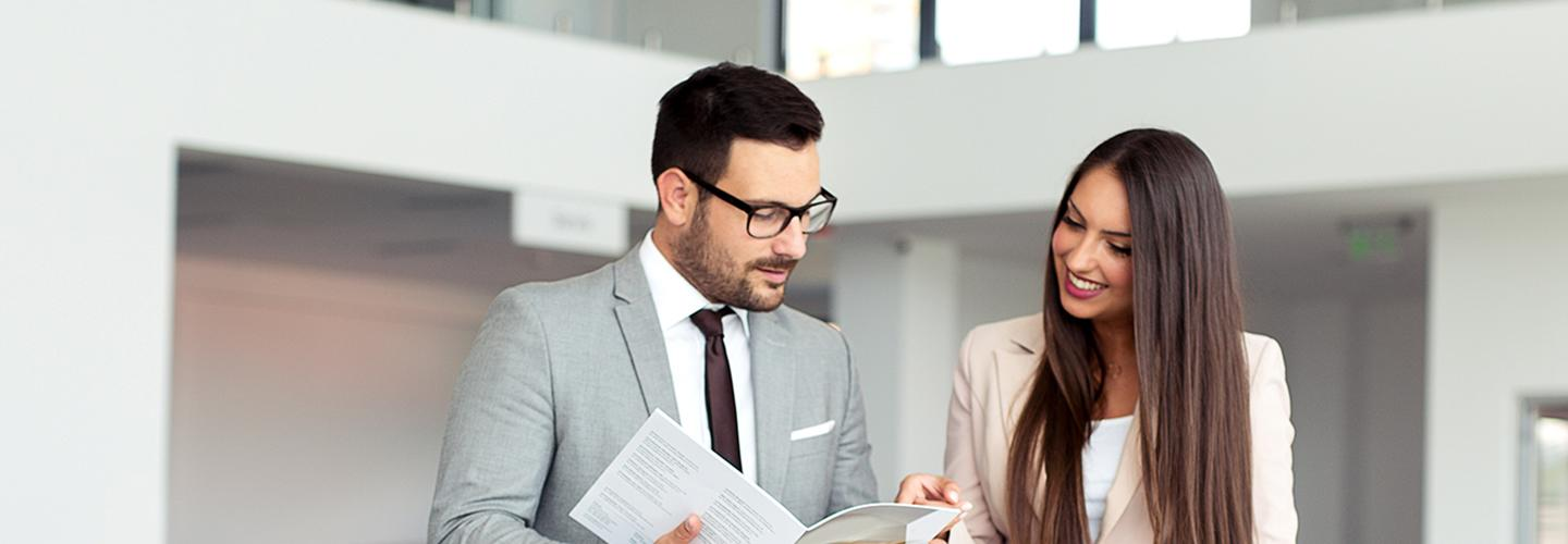 Two dealership employees reviewing paperwork