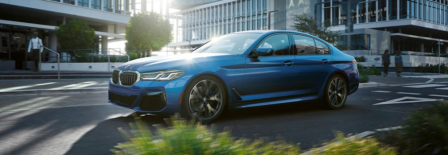 Side profile of a blue BMW vehicle in motion