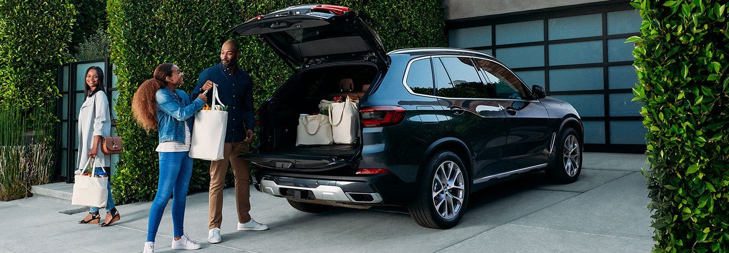 People taking luggages out of BMW Trunk