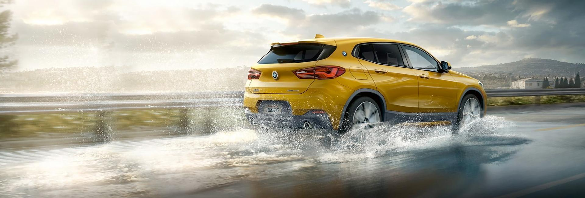 Rear view of the 2021 BMW X2 in motion in the rain