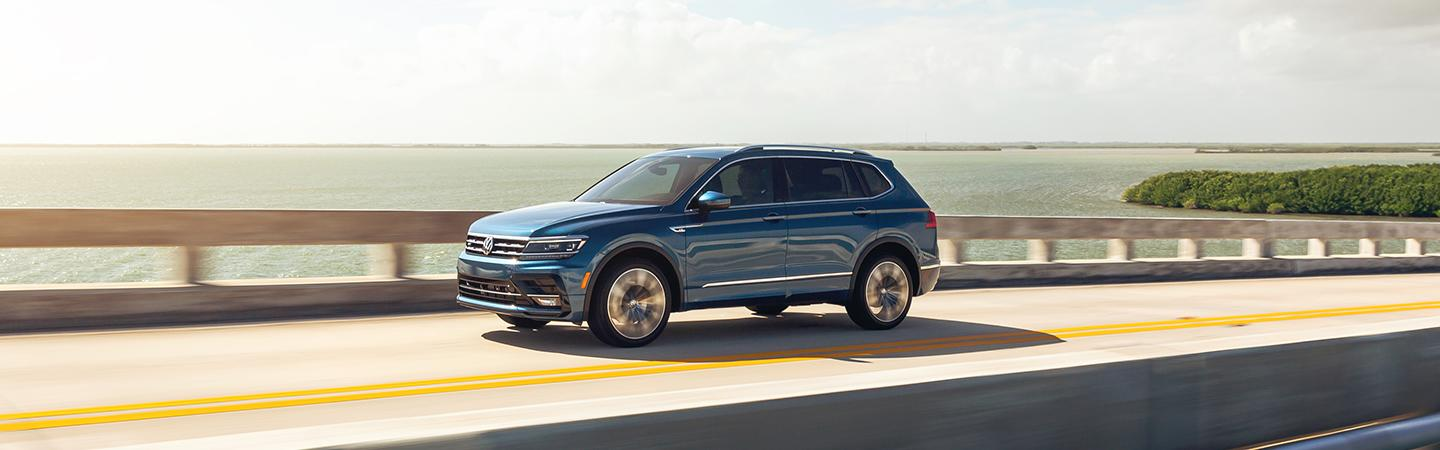 A Blue 2021 Tiguan riding over a bridge