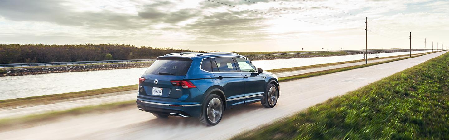 Rear driver profile of a blue 2021 Tiguan over a bridge
