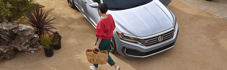 A women walking in front of a 2021 Passat