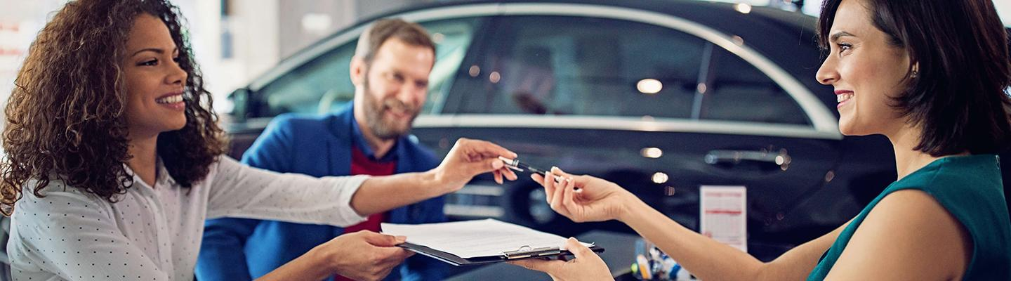 New VW customers signing their new VW's paperwork at the dealership