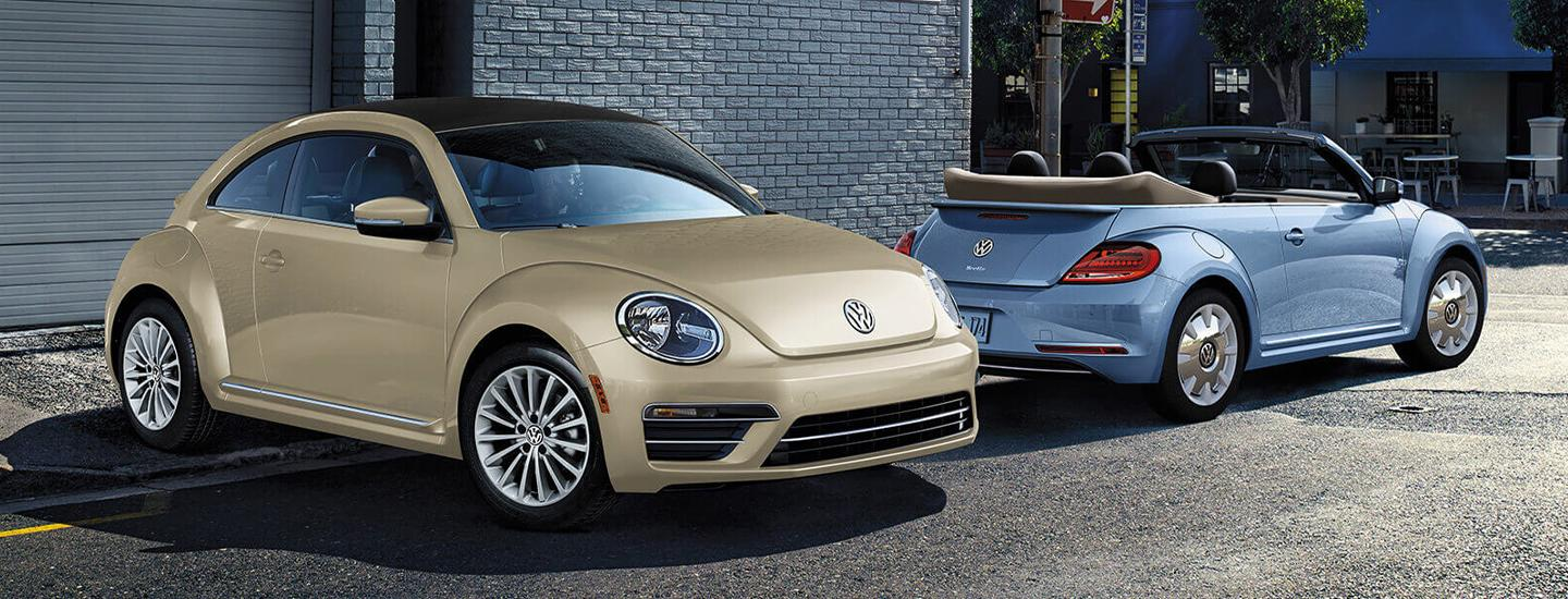 Pair of 2019 Volkswagen Beetles parked next to a building.