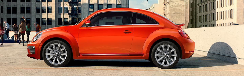 Orange 2019 Volkswagen Beetle Parked in a parking spot.