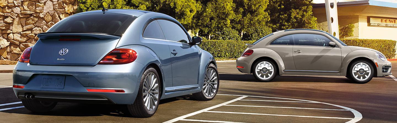 Pair of 2019 Volkswagen Beetles parked in parking spaces.