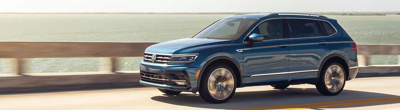 A blue 2021 Volkswagen Tiguan in motion through a bridge.